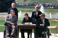 President George H.W. Bush signs the Americans with Disabilities Act on the White House lawn surrounded by Evan Kemp, the Rev. Harold Wilke, Justin Dart Jr., and Sandra Parrino.