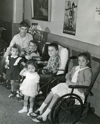 Children of various ages sit in a hallway, several of them in wheelchairs.